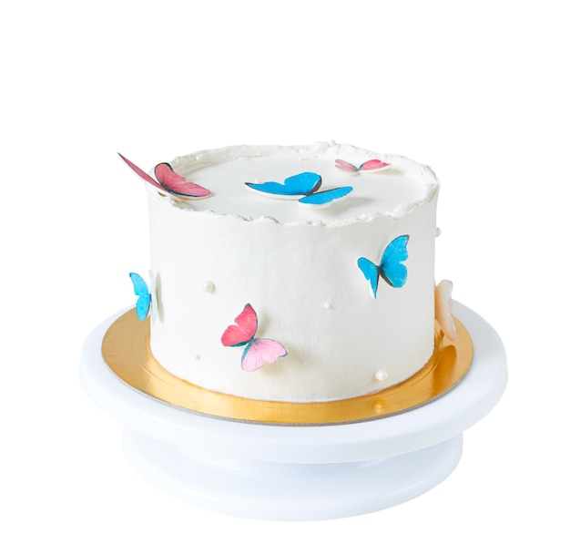 Pastel blanco decorado con mariposas azules y rosas aisladas sobre fondo blanco.