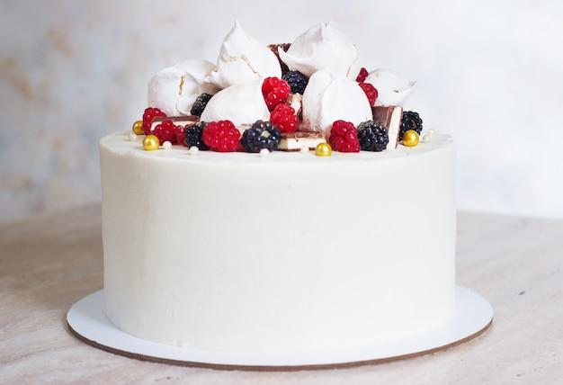 Pastel blanco festivo con merengue y bayas