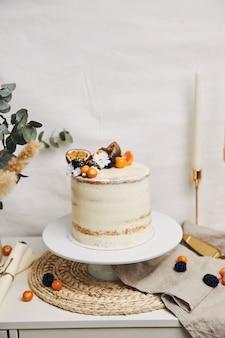 Pastel blanco con frutos rojos y maracuyá junto a una planta