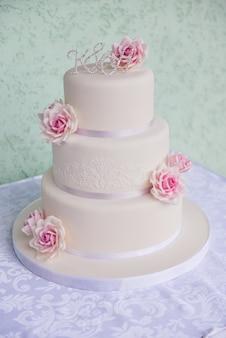 Pastel de boda de tres niveles con rosas rosadas hechas de masilla se coloca sobre la mesa