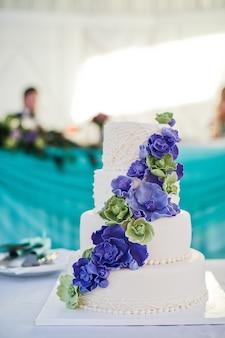 Pastel de bodas blanco decorado con flores azules.
