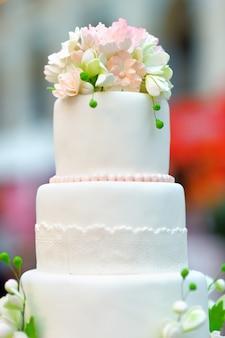 Pastel de bodas blanco decorado con flores color crema.