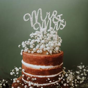 Pastel de bodas con decoración de paniculata y sr. y sra. topper sobre fondo verde