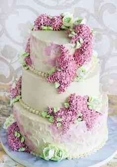 Pastel de bodas festivas con flores de color lila sobre fondo blanco.