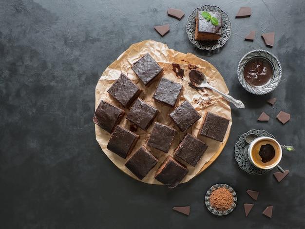 Pastel de brownie de chocolate con café negro, postre en mesa negra