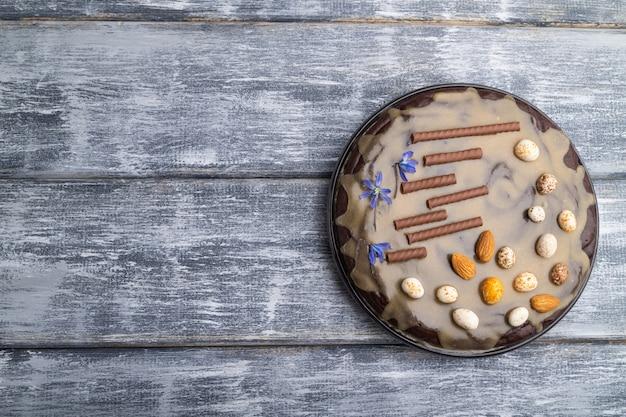 Pastel de brownie de chocolate casero con crema de caramelo y almendras sobre un fondo de madera gris. vista superior.