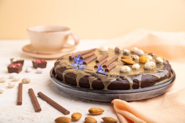 Pastel de brownie de chocolate casero con crema de caramelo y almendras con una taza de café sobre un fondo blanco y naranja. vista lateral, enfoque selectivo, copia espacio.