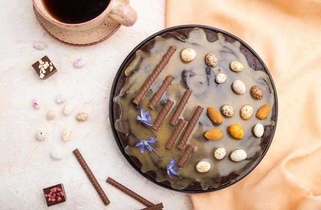 Pastel de brownie de chocolate casero con crema de caramelo y almendras con una taza de café sobre un fondo de hormigón blanco. vista superior, primer plano