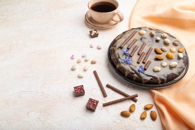 Pastel de brownie de chocolate casero con crema de caramelo y almendras con una taza de café sobre un fondo de hormigón blanco.