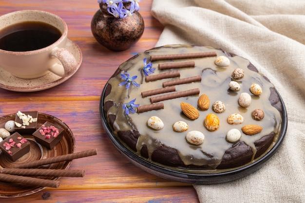 Pastel de brownie de chocolate casero con crema de caramelo y almendras con una taza de café sobre un fondo de madera coloreada. vista lateral, de cerca.