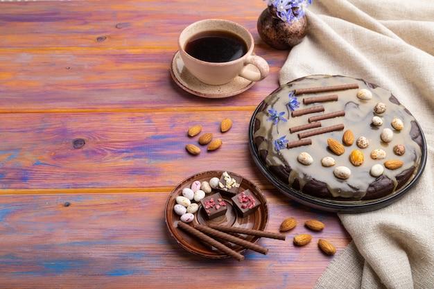 Pastel de brownie de chocolate casero con crema de caramelo y almendras con una taza de café sobre un fondo de madera coloreada.