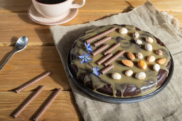 Pastel de brownie de chocolate casero con crema de caramelo y almendras con una taza de café sobre fondo de madera. vista lateral, luz dura.