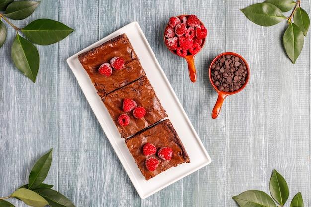 Pastel de brownie de chocolate rebanadas de postre con frambuesas y especias, vista superior