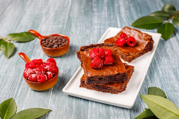 Pastel de brownie de chocolate, rebanadas de postre con frambuesas y especias