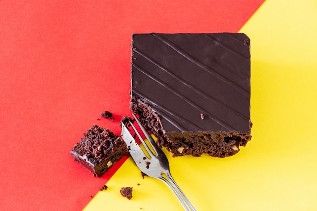 Pastel de brownie de chocolate vegano con nueces fondo de dos tonos naranja y amarillo