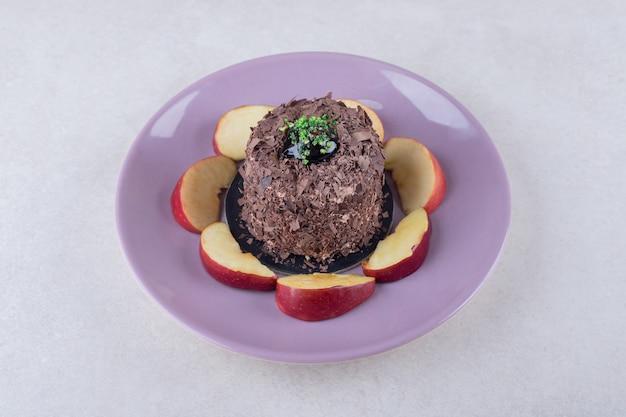Pastel de brownie y manzanas en rodajas en un plato sobre una mesa de mármol.