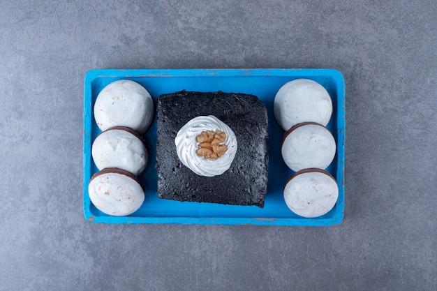 Pastel de brownie un mini pastel pop en placa de madera sobre mesa de mármol.