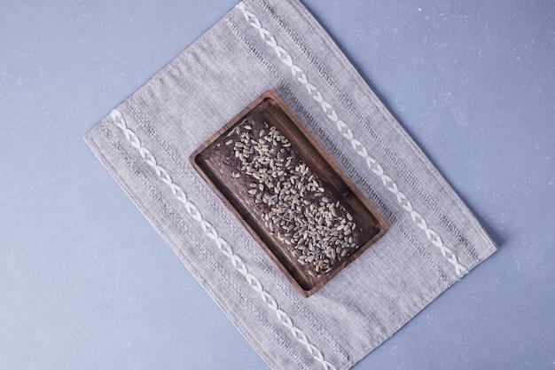 Pastel de brownie con semillas de girasol sobre un mantel.