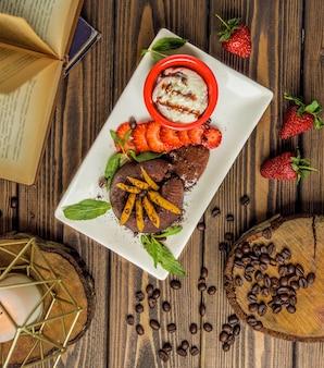 Pastel de brownie servido con helado de vainilla y frutas mentoladas