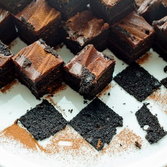 Pastel de brownies de chocolate en plato blanco con restos de brownies.