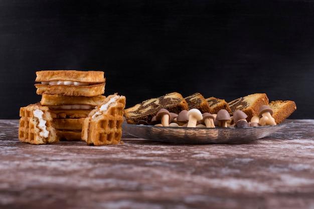 Pastel de cacao con gofres y galletas en una bandeja de vidrio sobre fondo negro