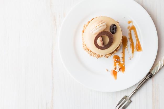 Pastel de café con caramelo en un glaseado con nueces en la placa sobre fondo blanco vista superior