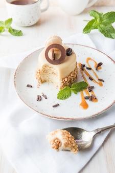 Pastel de café con caramelo en un glaseado con nueces en la placa sobre fondo blanco.
