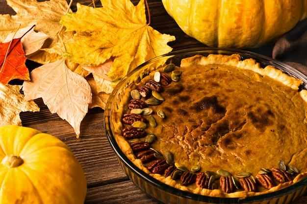 Pastel de calabaza casero tradicional decorado con nueces y semillas. fondo de madera de estilo rústico natural.