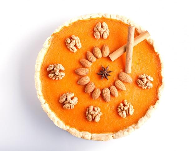 Pastel de calabaza dulce americano tradicional decorado con frutos secos, aislados en superficie blanca.