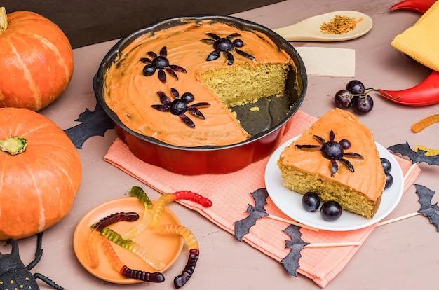 Pastel de calabaza para halloween con calabazas, decorado con dulces sobre una superficie de madera
