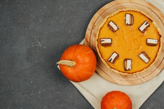 Pastel de calabaza sobre una plancha de madera y pequeñas calabazas sobre un fondo gris oscuro. trato de halloween.