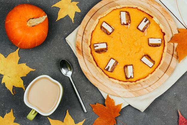 Pastel de calabaza en una tabla de madera, pequeñas calabazas naranjas, hojas de arce otoñal y una taza de café