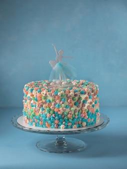 Pastel de capas de cumpleaños decorado con adorno de pastel de bailarina sobre fondo azul cielo
