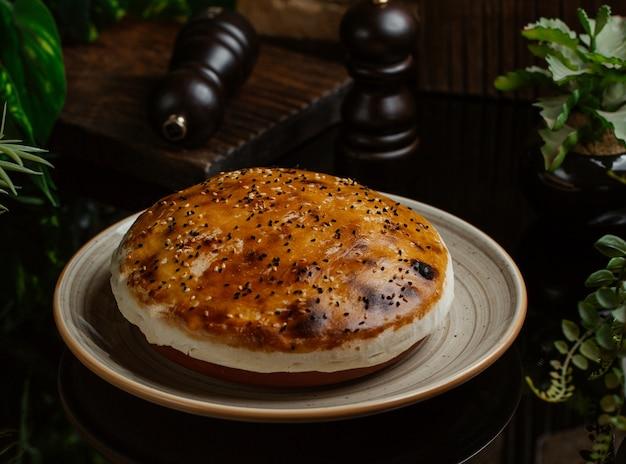 Pastel de carne, redondo, cubierto con yema de huevo y finamente cocido