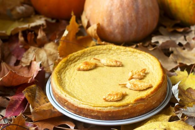 Pastel casero tradicional de calabaza estadounidense, decorado con galletas sobre un fondo de calabazas y hojas de otoño.