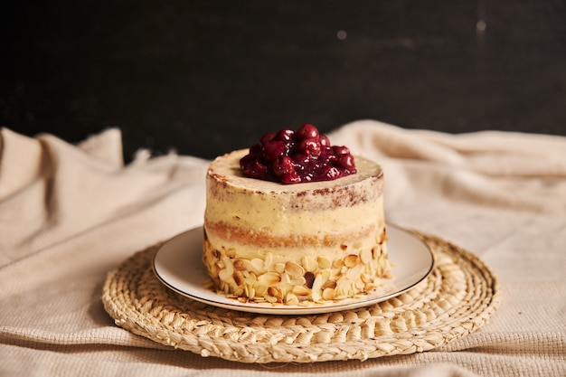Pastel de cereza con crema sobre un plato blanco con un fondo borroso