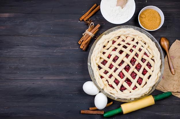 Pastel de cereza cruda en forma redonda de vidrio e ingredientes