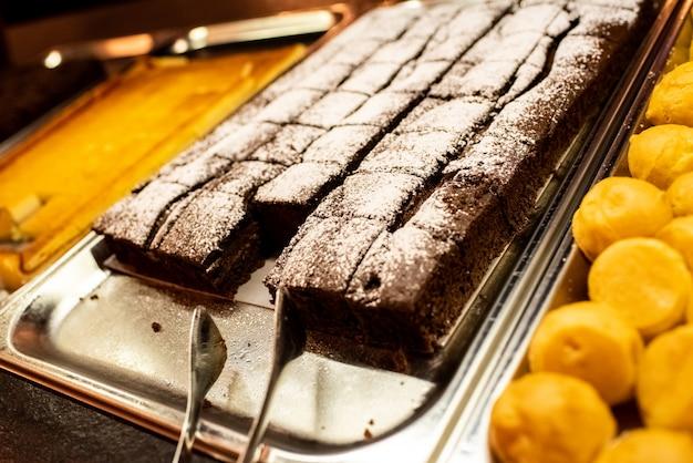 Pastel de chocolate en una bandeja en un restaurante de autoservicio
