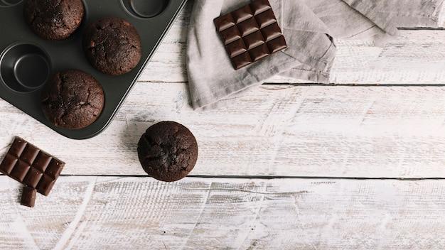 Pastel de chocolate con barra en mesa de madera blanca