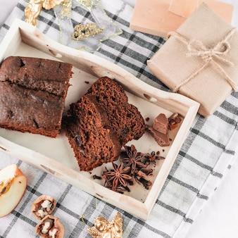 Pastel de chocolate con canela en bandeja de madera.