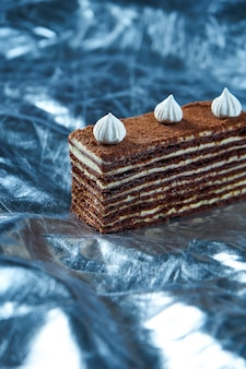 Pastel de chocolate con capas y crema pastelera en mesa de plata. rebanada de delicioso. galleta. de cerca. concepto de panadería sabrosa. enfoque selectivo