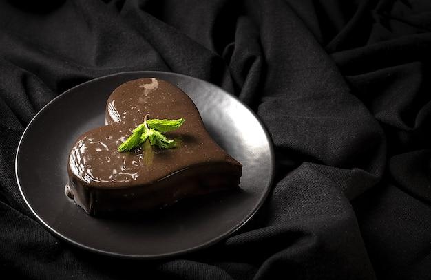 Pastel de chocolate casero en forma de corazón sobre fondo negro