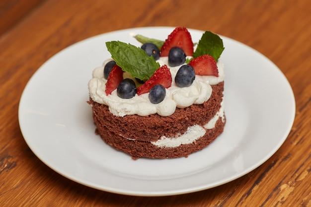 Pastel de chocolate con crema y bayas en plato blanco