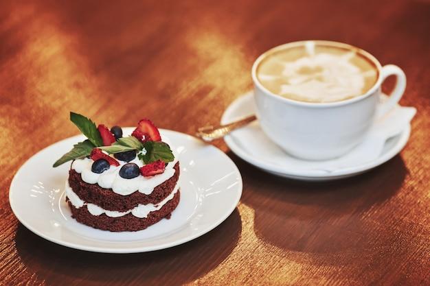Pastel de chocolate con crema, bayas y una taza de café con leche