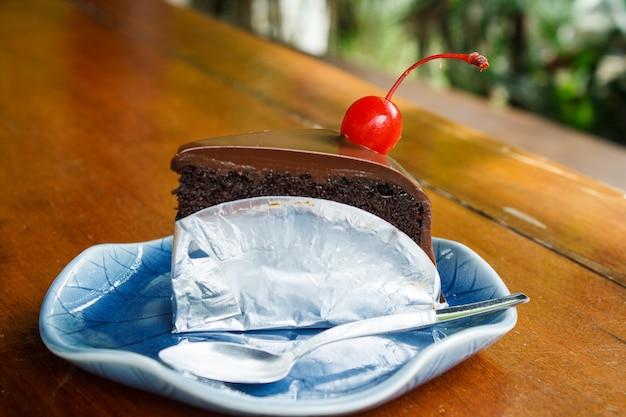 Pastel de chocolate decorado con cerezas en platos azules y cuchara