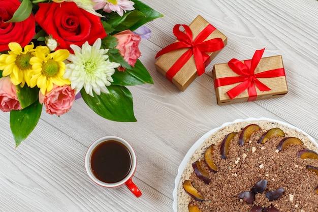 Pastel de chocolate decorado con ciruelas, un ramo de flores, cajas de regalo y una taza de café en las tablas de madera gris