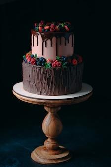 Pastel de chocolate de frutas en soporte de madera en negro.