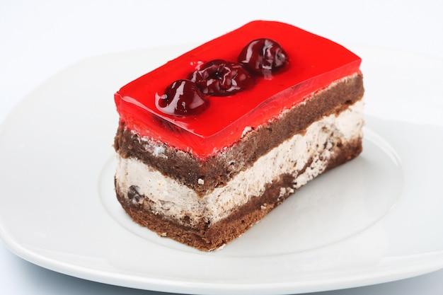 Pastel de chocolate con guindas en plato blanco