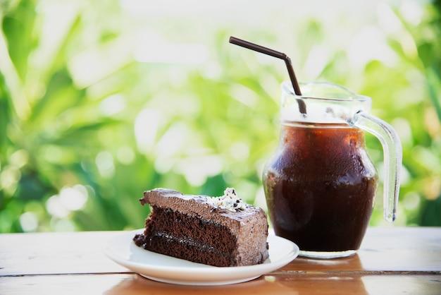 Pastel de chocolate en la mesa con café con hielo sobre jardín verde - relájese con una bebida y una panadería en concepto de naturaleza