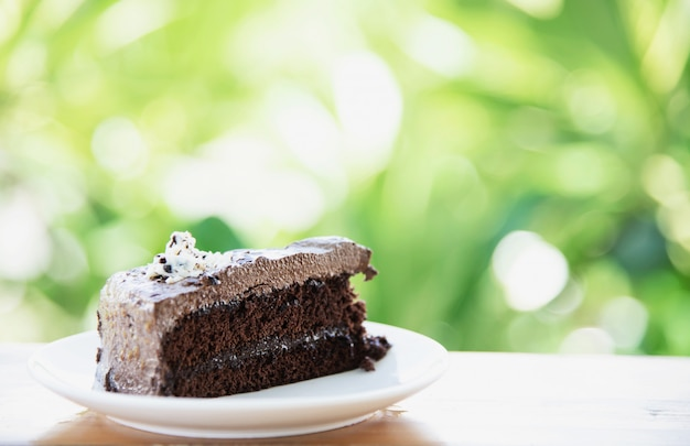 Pastel de chocolate en la mesa con jardín verde - relájese con el concepto de panadería y naturaleza